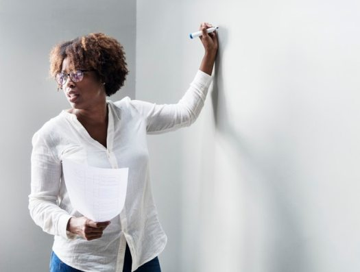 A women of a minority group teaching at a whiteboard